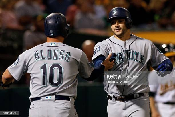 Mike Zunino of the Seattle Mariners is congratulated by Yonder Alonso after hitting a three run home run against the Oakland Athletics during the...