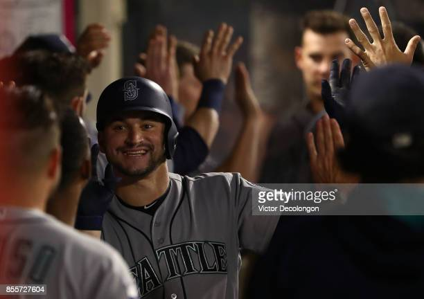 Mike Zunino of the Seattle Mariners smiles as he celebrates with teammates in the dugout after hitting a tworun homerun during the sixth inning of...