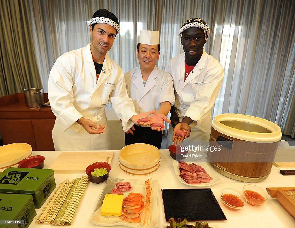 Mikel Arteta (L) and Bacary Sagna (R) of Arsenal FC are given a lesson in making Sushi from a top Sushi Chef in the Urawa Royal Pines Hotel in Japan for the club's pre-season Asian tour on July 25, 2013 in Saitama, Japan.