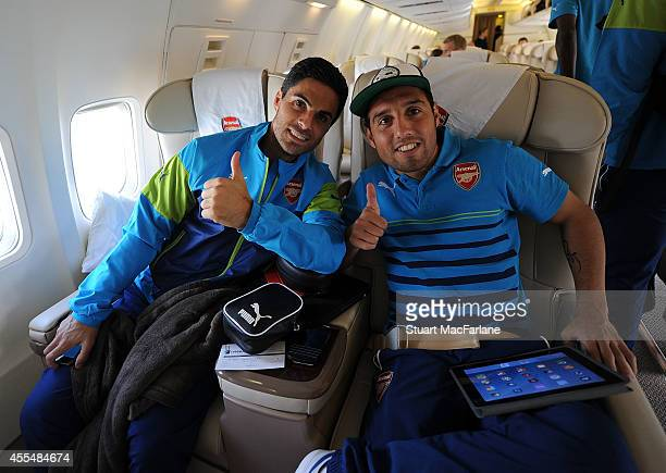 Mikel Arteta and Santi Cazorla of Arsenal on the team plane at Luton Airport on September 15 2014 in St Albans England Photo by Stuart...