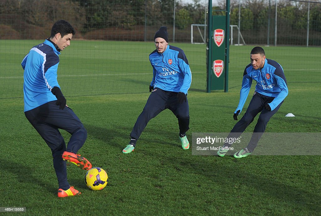 Mikel Arteta, Nicklas Bendtner and Alex Oxlade-Chambelrain of Arsenal during a training session at London Colney on January 27, 2014 in St Albans, England.