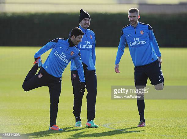 Mikel Arteta Nicklas Bendtner and Per Mertesacker of Arsenal during a training session at London Colney on February 1 2014 in St Albans England