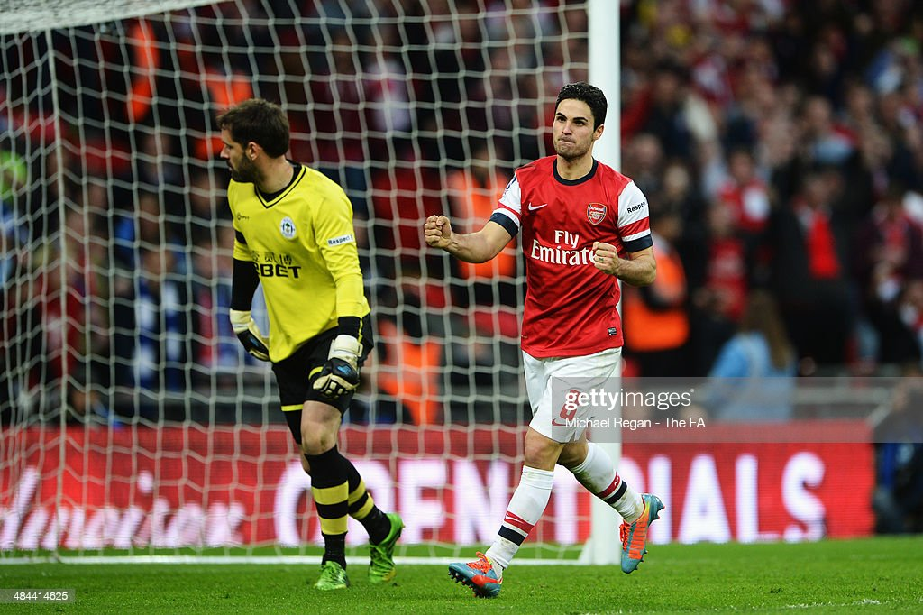 Mikel Arteta of Arsenal celebrates after scoring during the penalty shoot-out to claim victory in the FA Cup Semi-Final match between Wigan Athletic and Arsenal at Wembley Stadium on April 12, 2014 in London, England.