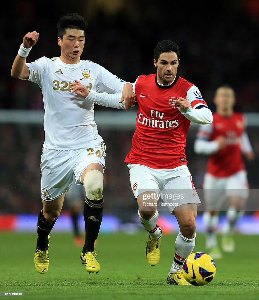 Mikel Arteta of Arsenal holds off Ki Sung-Yong of Swansea during the Barclays Premier League match between Arsenal and Swansea City at the Emirates Stadium on December 1, 2012 in London, England.