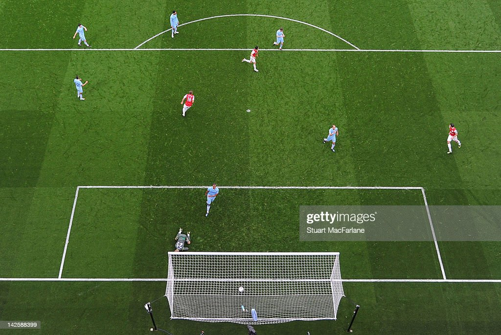 Mikel Arteta of Arsenal (top left) shoots past Manchester City goalkeeper Joe Hart to score the only goal of the match during the Barclays Premier League match between Arsenal and Manchester City at Emirates Stadium on April 8, 2012 in London, England.