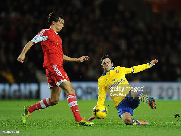 Mikel Arteta tackles Jack Cork of Southampton during the match between Southampton and Arsenal at St Mary's Stadium on January 28 2014 in Southampton...