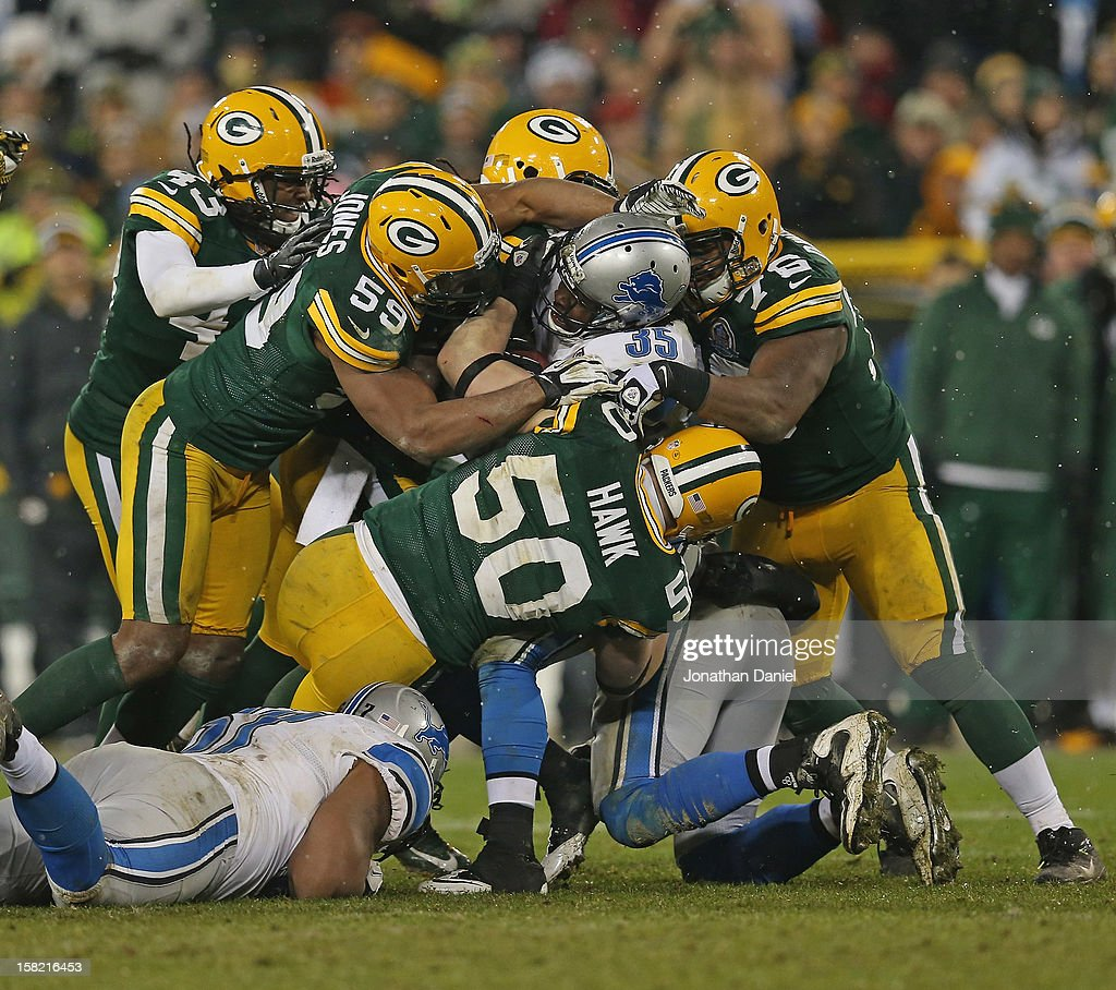 Mikel Leshoure #25 of the Detroit Lions is gang-tackled by members of the Green Bay Packer defense including Brad Jones #59, A.J. Hawk #50 and Mike Daniels #76 at Lambeau Field on December 9, 2012 in Green Bay, Wisconsin. The Packers defeated the Lions 27-20.