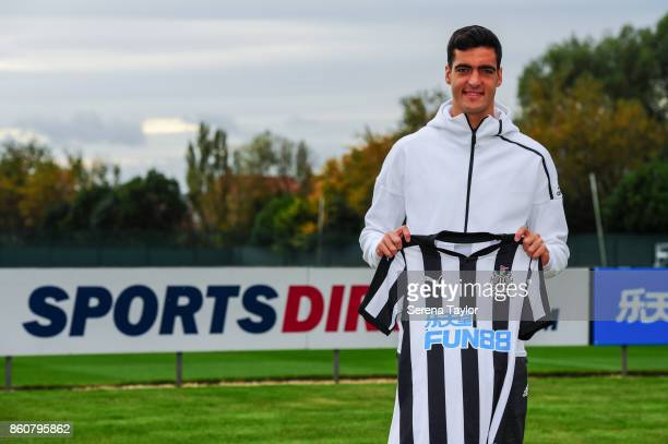 Mikel Merino poses for a photograph holding a home shirt after signing a permanent contract at the Newcastle United Training Centre on October 13 in...