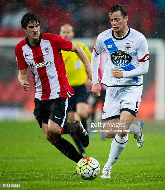 Mikel San Jose of Athletic Club Bilbao competes for the ball with Oriol Riera of Deportivo La Coruna during the La Liga match between Athletic Club...