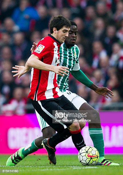Mikel San Jose of Athletic Club Bilbao competes for the ball with Alfred N'Diaye of Real Betis Balompie during the La Liga match between Athletic...