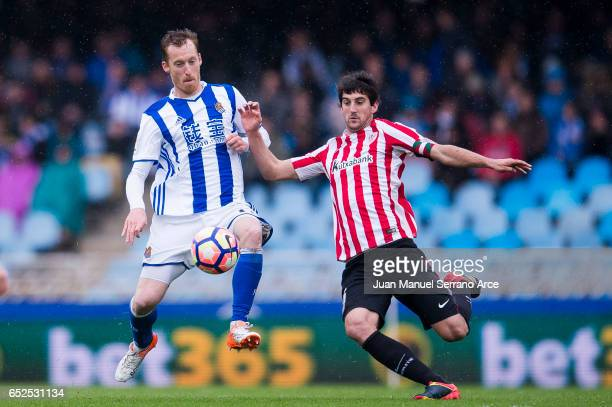 Mikel San Jose of Athletic Club Bilbao duels for the ball with David Zurutuza of Real Sociedad during the La Liga match between Real Sociedad de...
