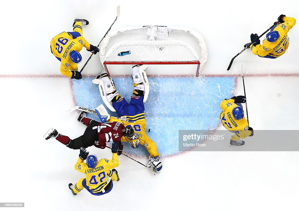 Mikelis Redlihs #24 of Latvia falls to the ice while trying to score against Jimmie Ericsson #42 and Henrik Lundqvist #30 of Sweden in the second period during the Men's Ice Hockey Preliminary Round Group C game on day eight of the Sochi 2014 Winter Olympics at Shayba Arena on February 15, 2014 in Sochi, Russia.