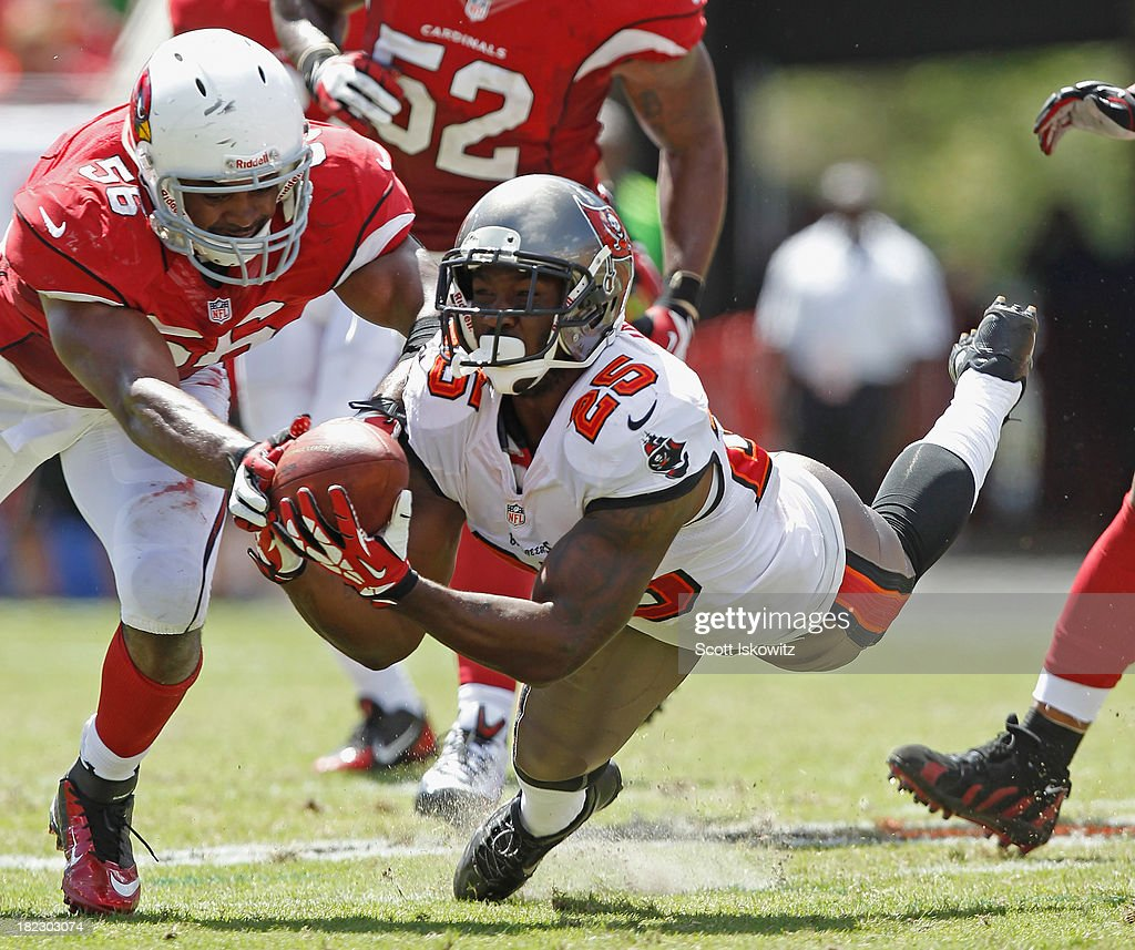 Mikes James #25 of the Tampa Bay Buccaneers makes a diving catch against <a gi-track='captionPersonalityLinkClicked' href=/galleries/search?phrase=Karlos+Dansby&family=editorial&specificpeople=233759 ng-click='$event.stopPropagation()'>Karlos Dansby</a> #56 of the Arizona Cardinals during the 2nd quarter at Raymond James Stadium on September 29, 2013 in Tampa, Florida.