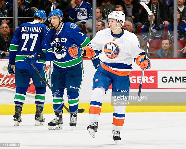 Mikhail Grabovski of the New York Islanders celebrates scoring in front of Luca Sbisa and Shawn Matthias of the Vancouver Canucks during their NHL...