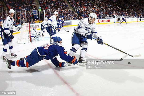 Mikhail Grabovski of the New York Islanders falls to the ice in pursuit of Jonathan Drouin of the Tampa Bay Lightning at Nassau Veterans Memorial...