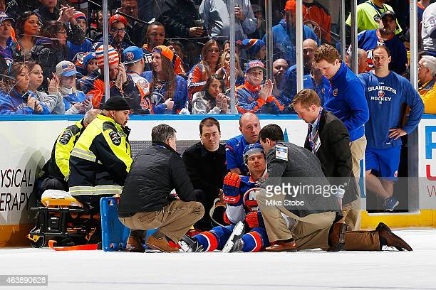 Mikhail Grabovski of the New York Islanders is tended to by medical staff after being checked by Eric Nystrom of the Nashville Predators at Nassau...