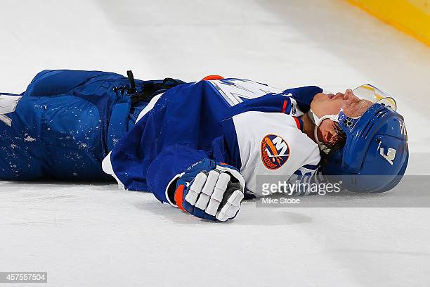 Mikhail Grabovski of the New York Islanders lays on the ice after getting hit in a game against San Jose Sharks at Nassau Veterans Memorial Coliseum...