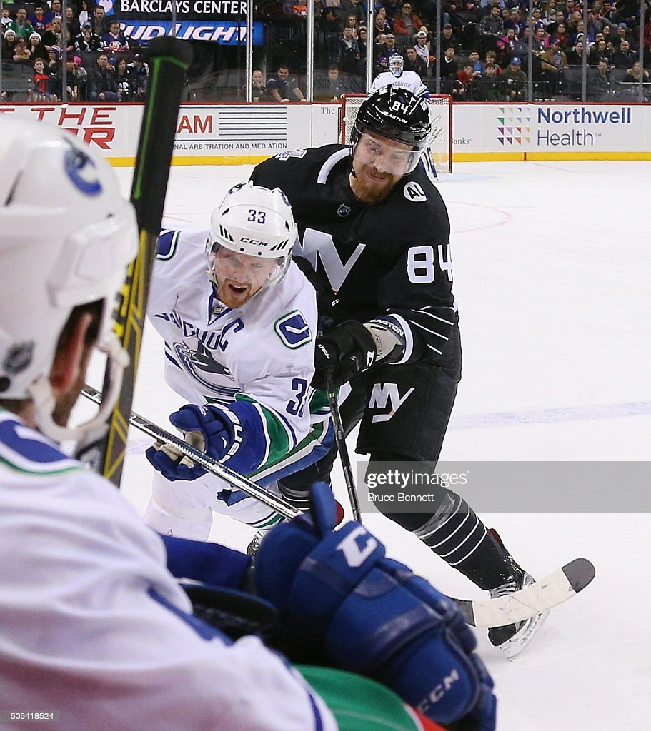<a gi-track='captionPersonalityLinkClicked' href=/galleries/search?phrase=Mikhail+Grabovski&family=editorial&specificpeople=2560547 ng-click='$event.stopPropagation()'>Mikhail Grabovski</a> #84 of the New York Islanders takes a major penalty for boarding against <a gi-track='captionPersonalityLinkClicked' href=/galleries/search?phrase=Henrik+Sedin&family=editorial&specificpeople=202574 ng-click='$event.stopPropagation()'>Henrik Sedin</a> #33 of the Vancouver Canucks during the first period at the Barclays Center on January 17, 2016 in the Brooklyn borough of New York City.