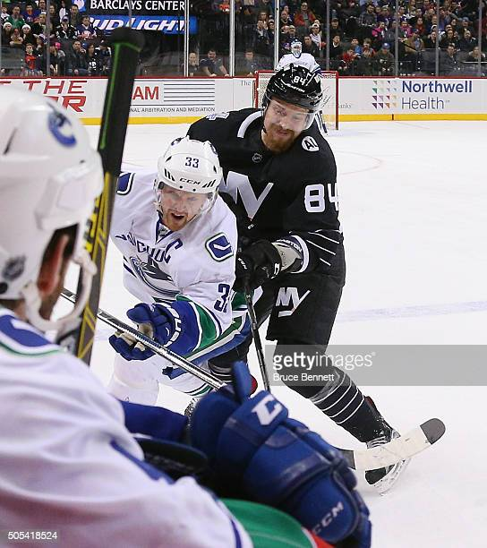 Mikhail Grabovski of the New York Islanders takes a major penalty for boarding against Henrik Sedin of the Vancouver Canucks during the first period...