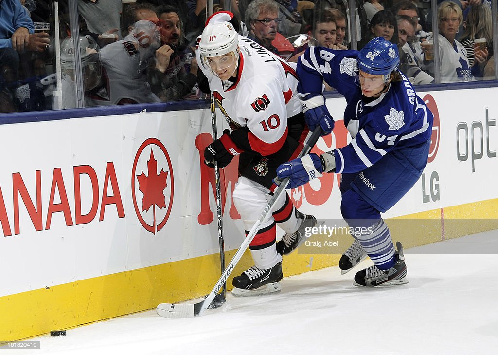 Mikhail Grabovski #84 of the Toronto Maple Leafs battles for the puck with Mike Lundin #10 of the Ottawa Senators during NHL game action February 16, 2013 at the Air Canada Centre in Toronto, Ontario, Canada.