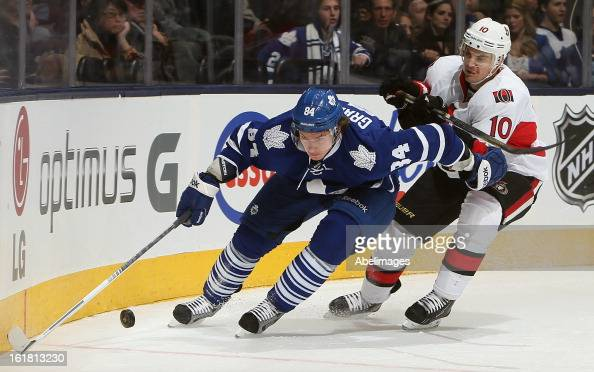 Mikhail Grabovski of the Toronto Maple Leafs fights off Mike Lundin of the Ottawa Senators during NHL action at the Air Canada Centre February 16...
