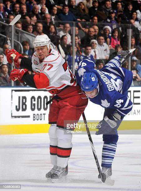 Mikhail Grabovski of the Toronto Maple Leafs is checked by Joe Corvo of the Carolina Hurricanes during game action February 3 2011 at the Air Canada...