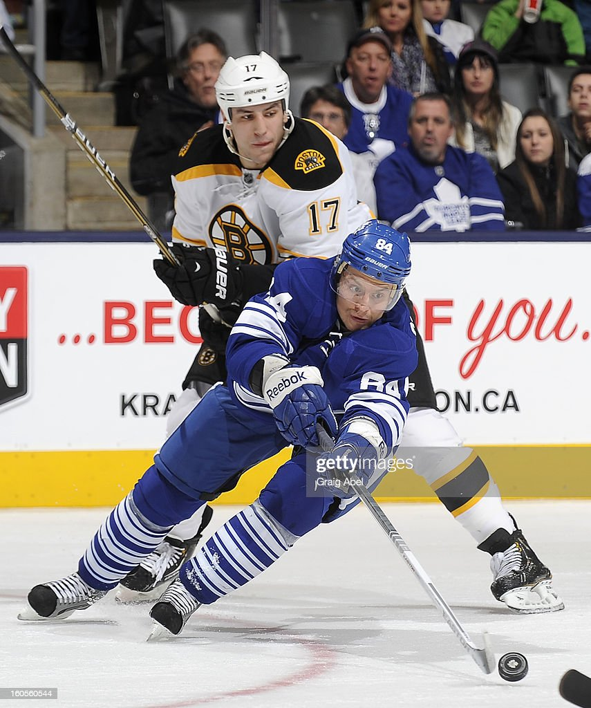 Mikhail Grabovski #84 of the Toronto Maple Leafs skates the puck away from Milan Lucic #17 of the Boston Bruins during NHL game action February 2, 2013 at the Air Canada Centre in Toronto, Ontario, Canada.