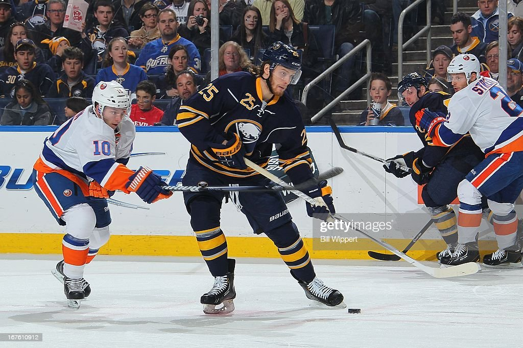 Mikhail Grigorenko #25 of the Buffalo Sabres looks to shoot the puck as Keith Aucoin #10 of the New York Islanders reaches in from behind on April 26, 2013 at the First Niagara Center in Buffalo, New York.
