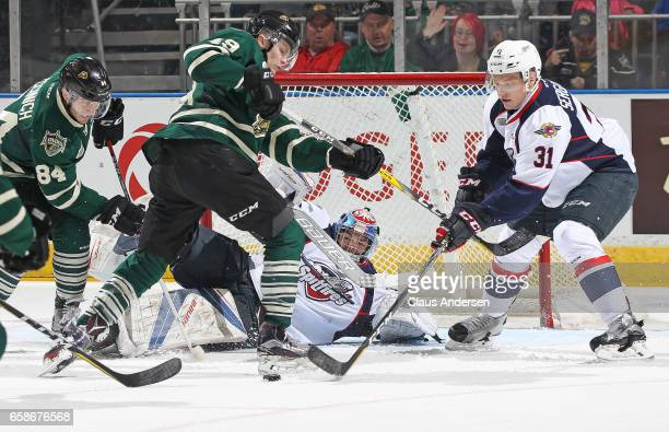 Mikhail Sergachev of the Windsor Spitfires looks to clear a puck away from Max Jones of the London Knights during Game Two of the OHL Western...