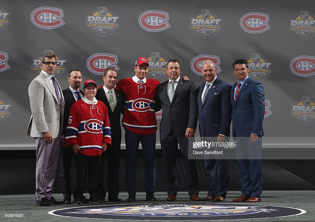 Mikhail Sergachev poses with team personnel after being selected ninth overall by the Montreal Canadiens during round one of the 2016 NHL Draft at First Niagara Center on June 24, 2016 in Buffalo, New York.
