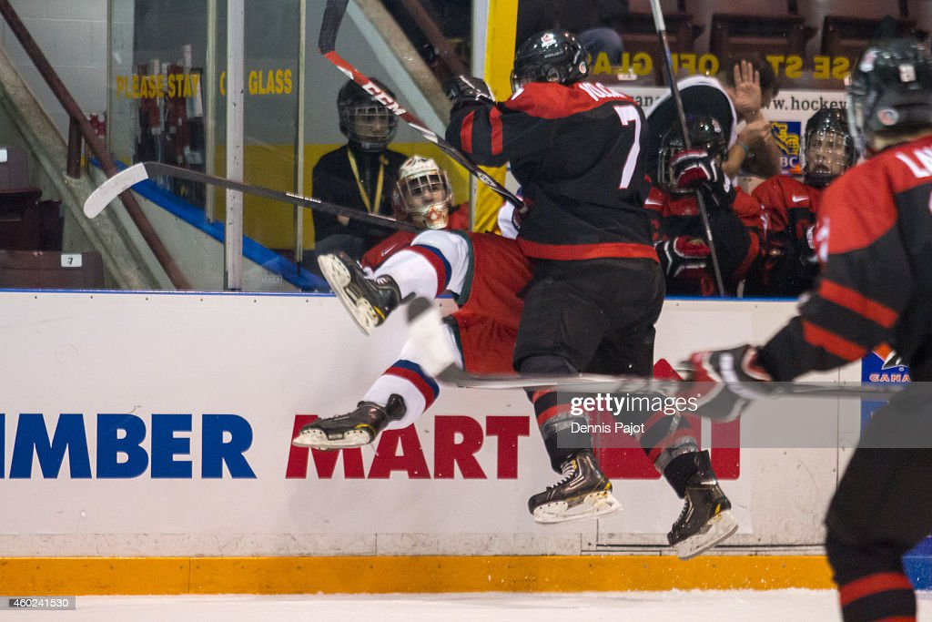 Mikhail Shabanov #14 of Russia is checked into the stanchion next to the bench by Nolan Volcan #7 of Canada Black during the World Under-17 Hockey Challenge on November 2, 2014 at the RBC Centre in Sarnia, Ontario.