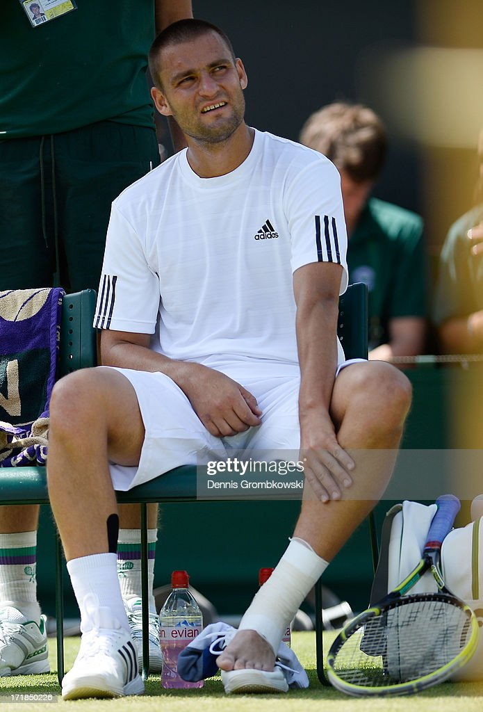 Mikhail Youzhny of Russia holds his leg during a break in his Gentlemen's Singles third round match against Viktor Troicki of Serbia on day six of the Wimbledon Lawn Tennis Championships at the All England Lawn Tennis and Croquet Club on June 29, 2013 in London, England.