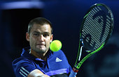 Mikhail Youzhny of Russia plays a backhand against Roger Federer of Switzerland during day one of the ATP Dubai Duty Free Tennis Championships at the...
