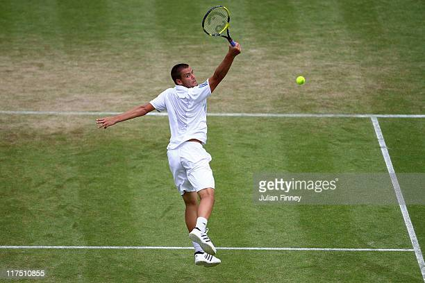 Mikhail Youzhny of Russia reaches for a shot during his fourth round match against Roger Federer of Switzerland on Day Seven of the Wimbledon Lawn...