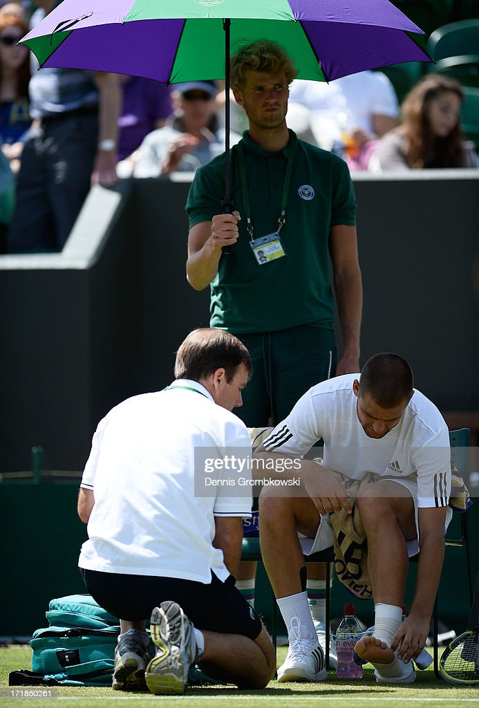 Mikhail Youzhny of Russia receives assistance for a foot injury during a break in his Gentlemen's Singles third round match against Viktor Troicki of Serbia on day six of the Wimbledon Lawn Tennis Championships at the All England Lawn Tennis and Croquet Club on June 29, 2013 in London, England.