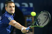 Mikhail Youzhny of Russia returns the ball to Roger Federer of Switzerland during their match in the first day of the ATP Dubai Duty Free Tennis...