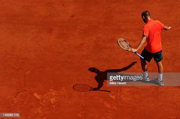Mikhail Youzhny of Russia writes a message in the clay with his shoe during his men's singles third round match against David Ferrer of Spain during...