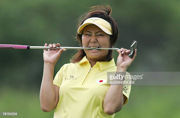 Miki Saiki of Japan reacts to the sound of a horn stoping stopping the game due to rain during day one of the Women's World Cup of Golf 18 January...