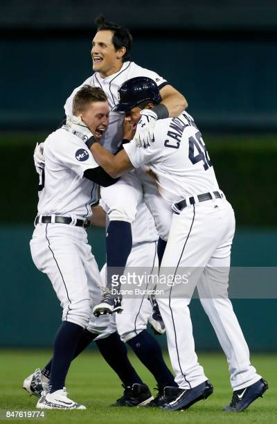 Mikie Mahtook of the Detroit Tigers is carried by JaCoby Jones of the Detroit Tigers and Jeimer Candelario of the Detroit Tigers after hitting a...