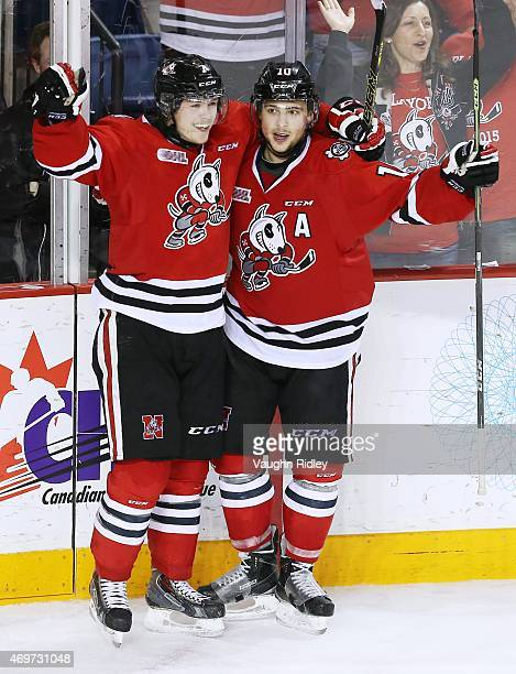 Mikkel Aagaard of the Niagara IceDogs celebrates an empty net goal with teammate Anthony DiFruscia during Game 3 of the Eastern Conference SemiFinals...
