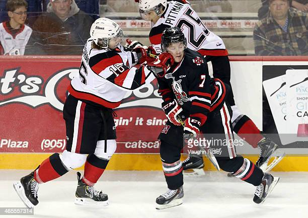 Mikkel Aagaard of the Niagara IceDogs is checked by Connor Graham of the Ottawa 67's during an OHL game at the Meridian Centre on March 7 2015 in St...