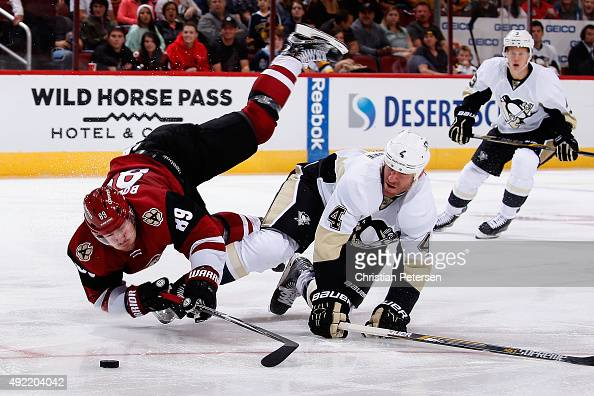 Mikkel Boedker of the Arizona Coyotes is upended by Rob Scuderi of the Pittsburgh Penguins as he attempts to skate in with the puck during the third...