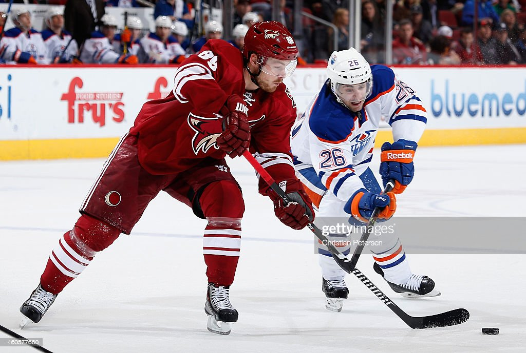 Mikkel Boedker #89 of the Arizona Coyotes passes the puck under pressure from Mark Arcobello #26 of the Edmonton Oilers during the NHL game at Gila River Arena on December 16, 2014 in Glendale, Arizona. The Coyotes defeated the Oilers 2-1 in overtime.