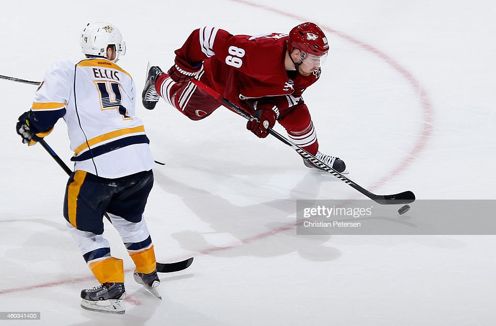 Mikkel Boedker #89 of the Arizona Coyotes skates with the puck past Ryan Ellis #4 of the Nashville Predators during the third period of the NHL game at Gila River Arena on December 11, 2014 in Glendale, Arizona. The Predators defeated the Coyotes 5-1.