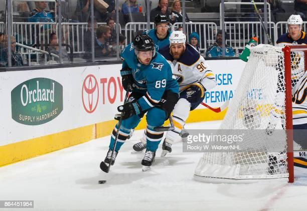 Mikkel Boedker of the San Jose Sharks skates behind the net against Ryan O'Reilly of the Buffalo Sabres at SAP Center on October 12 2017 in San Jose...