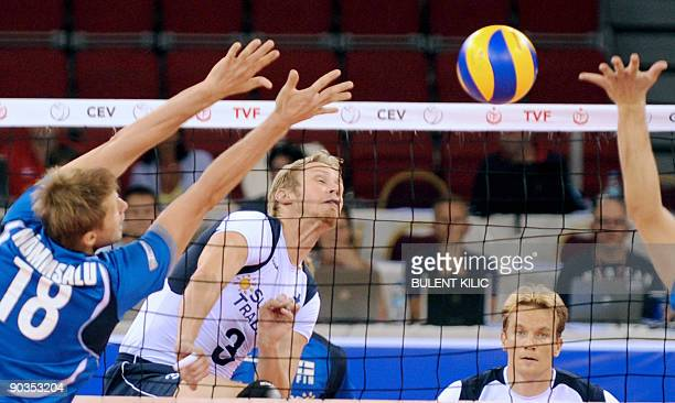 Mikko Esko of Finland spikes the ball over the net as Estonia`s Jaanus Nommsalu and Ardo Kreek jump to block it during their European Volleyball...