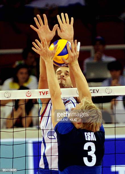 Mikko Esko of Finland spikes the ball over the net as Russia`s Alexander Volkov jumps to block it during their European Volleyball Championship match...