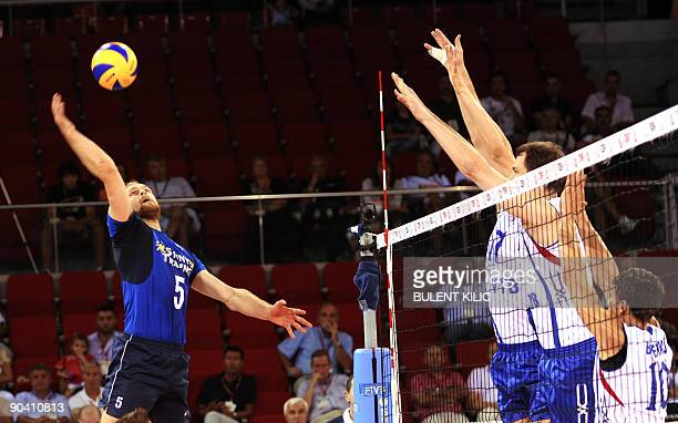 Mikko Esko of Finland spikes the ball over the net blocked by Russia`s Yury Brezhko and his teammates during their European Volleyball Championship...