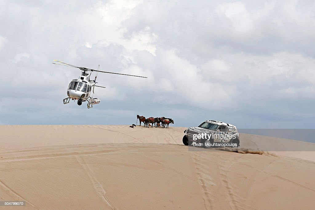 Mikko Hirvonen of Finland and Michel Perin of France in the MINI ALL4 RACING for AXION X-RAID TEAM are followed by the TV helicopter and go past some horses as they compete on day 11 stage ten between Belen and La Rioja during the 2016 Dakar Rally on January 13, 2016 in near Fiambala, Argentina.