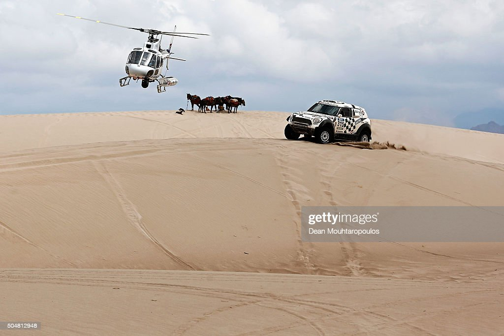 Mikko Hirvonen of Finland and Michel Perin of France in the MINI ALL4 RACING for AXION X-RAID TEAM are followed by the TV helicopter as they pass a group or team of horses while competing on day 11 stage ten between Belen and La Rioja during the 2016 Dakar Rally on January 13, 2016 in near Fiambala, Argentina.
